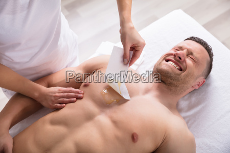 person waxing mans chest with wax