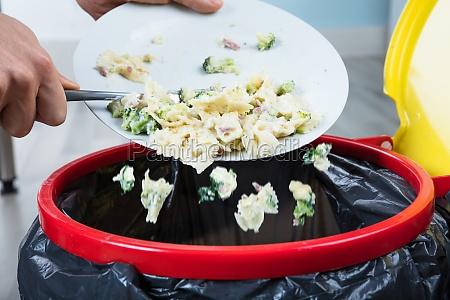 person die gekochte pasta in papierkorb