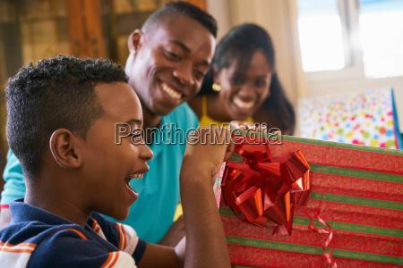 hispanic boy opening gift box happy
