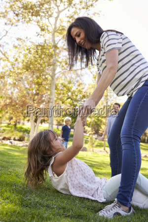 mother helping up daughter during family