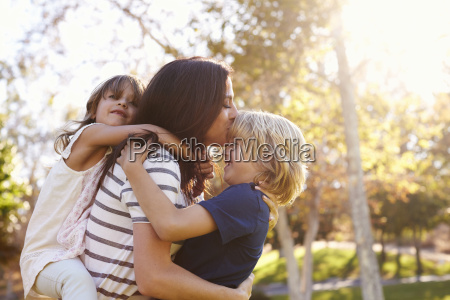 mother carrying son and daughter as