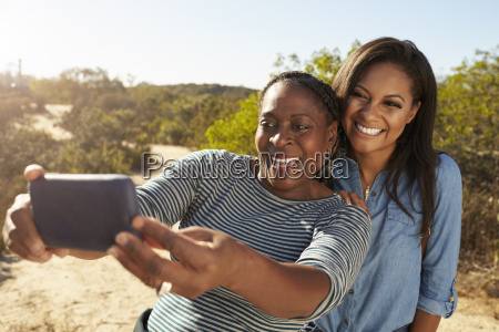 mother and adult daughter taking selfie