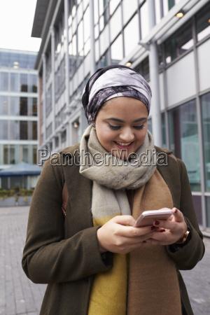 britische moslemische frau die auf handy