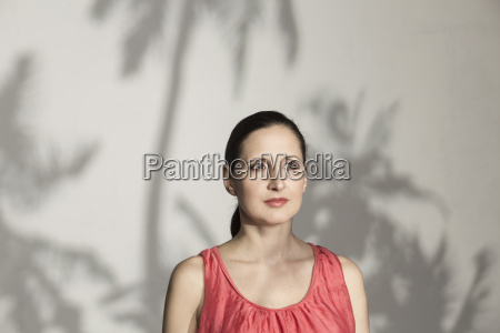 thoughtful mid adult woman against wall