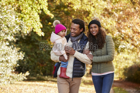 family with young daughter enjoying autumn