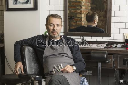 portrait of mature barber sitting on