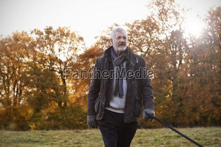 senior man taking dog for walk
