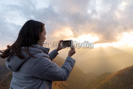 woman taking photo with cellphone at