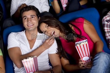 hispanic paar geniessen popcorn im kino