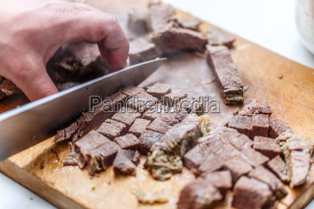 der koch schneidet gekochtes rindfleisch