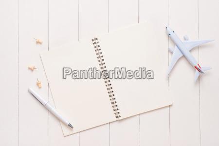 geschaeftsreisekonzept flugzeug und leere offene notizbuch
