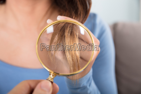 woman looking at her hair through