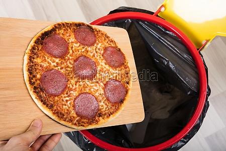 person die salami pizza in muelleimer