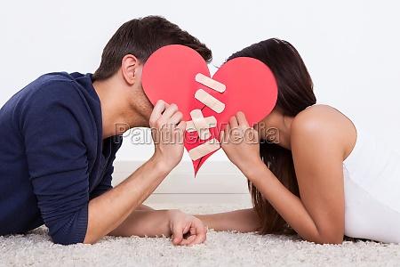 couple hiding behind heart shape at