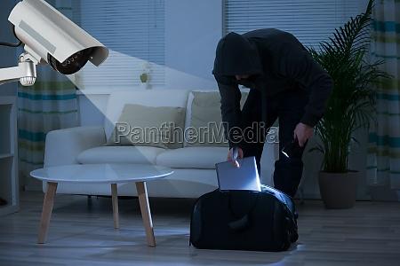 burglar putting laptop into bag at