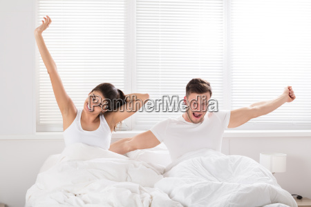 happy couple waking up on bed