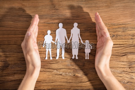 woman protecting family paper cut out