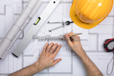 architect hands working on blueprint