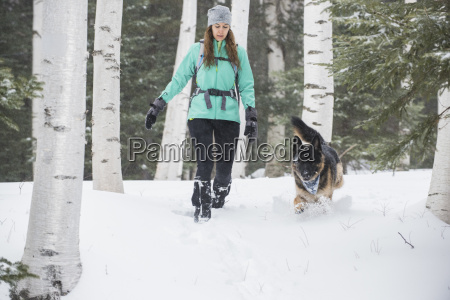 woman and dog running on snow