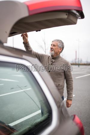 senior man by his car closing