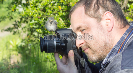 a photographer with a young songbird