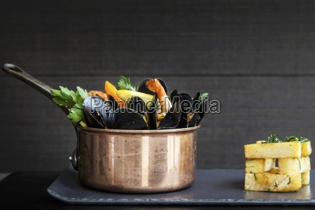 a copper saucepan of mussels with