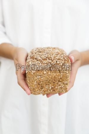 a woman holding a loaf of