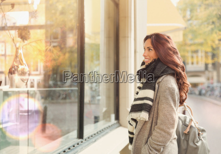 smiling young woman window shopping at