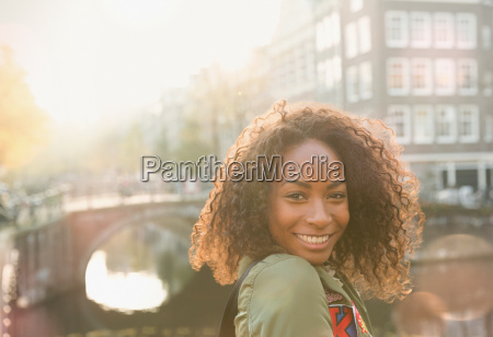 portrait smiling young woman along urban