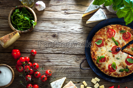 pizza on wood with ingredients