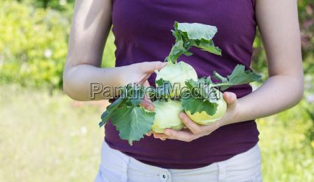 a girl holds tender fresh turnip