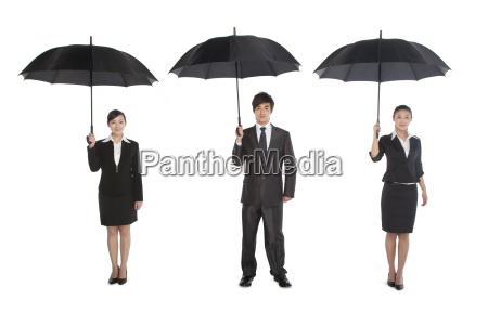 three business people holding umbrella