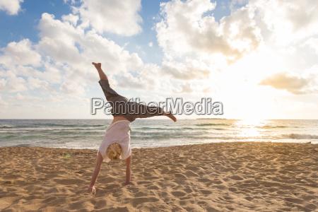 free happy woman turning cartwheel enjoying