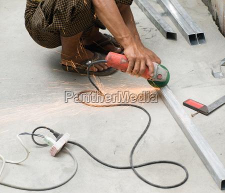 worker cutting steel mit electric wheel