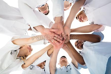 smiling medical team stacking haende