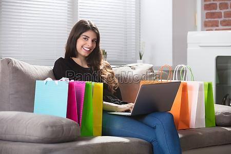glueckliche frau mit einkaufstaschen mit laptop