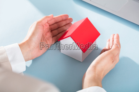businesswomans hand protecting miniature house