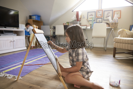 girl drawing on chalkboard in playroom