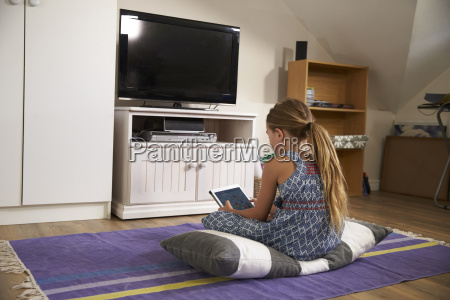girl watches television and using digital