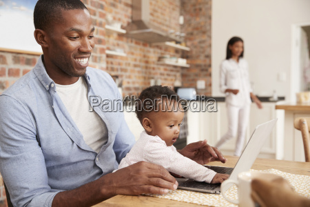 father and baby daughter use laptop
