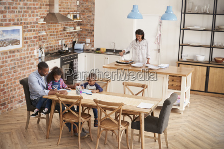 father and children drawing at table