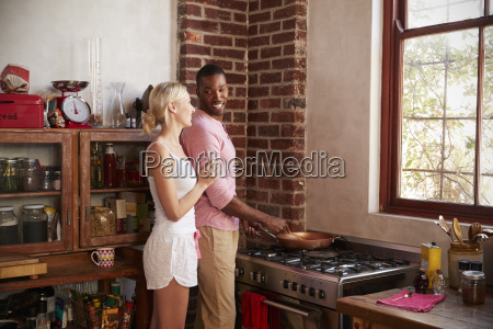 young mixed race couple preparing breakfast