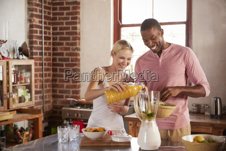 happy mixed race couple making smoothies