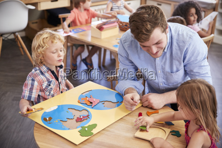 teacher and pupils using wooden shapes