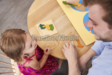 teacher and pupil using wooden shapes