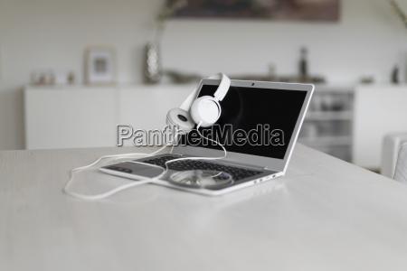 laptop kopfhoerer und cd auf tischplatte