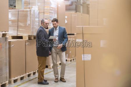 zwei maenner die tablette im fabriklager