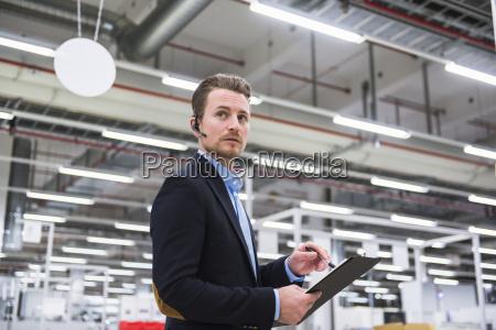 mann mit kopfhoerer im fabrikladenboden der