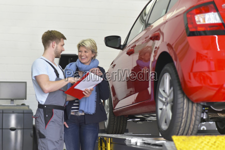 automechaniker mit kunden in der werkstatt
