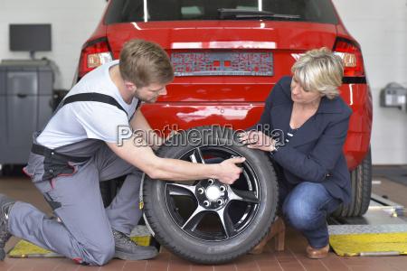 automechaniker mit kunden und reifen in
